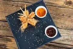 在kataifi面团和调味汁包裹的虾在板材 库存图片