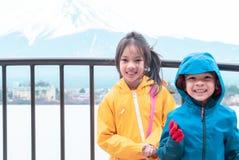 在Kawaguchiko湖和富士山前面的孩子身分在冬天 免版税图库摄影