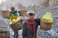 在Kawah伊真火山火山口里面的工作者运载的硫磺。印度尼西亚 库存照片