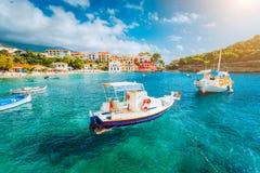 在Kefalonia海岛,希腊上的Assos村庄 在绿宝石的白色小船起了波纹海水海湾 库存图片