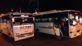 在kemer的两辆白色城市公共汽车在晚上 库存照片