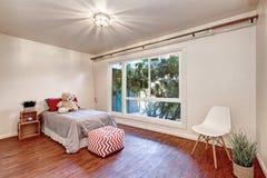 在kid& x27的白色墙壁; 有硬木地板的s卧室 库存照片