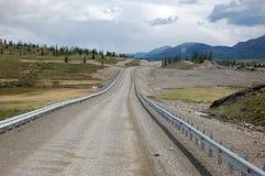 在Kolyma州际高速公路的石渣路 免版税库存图片