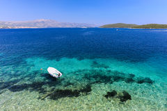在Korcula克罗地亚的清楚的蓝色海滩有小船的 库存照片