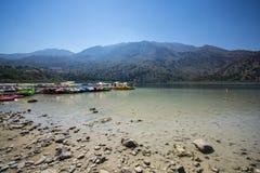 在Kournas蓝色湖的小船在山的背景中在克利特 免版税库存图片