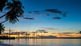 在Kri海岛上的日落 在Palmtrees下的小船 王侯Ampat,印度尼西亚,西部巴布亚 库存图片