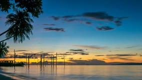 在Kri海岛上的日落 在Palmtrees下的小船 王侯Ampat,印度尼西亚,西部巴布亚 免版税图库摄影