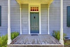 在Lakewood, WA打开与专栏和一个老房子的蓝色门的入口门廊 美国 库存图片