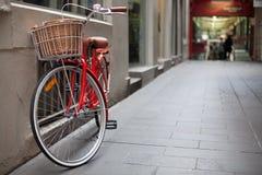 在laneway停放的一辆红色自行车 库存图片