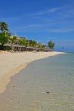 在Le Morne,有挥动的棕榈树的毛里求斯的普遍的海滩胜地和晒日光浴的小屋和非常清楚水 免版税图库摄影