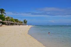 在Le Morne,毛里求斯,有挥动的棕榈树和晒日光浴的小屋的东非的普遍的海滩胜地 免版税库存图片