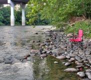 在Lehigh河,美国的河岸的便携式的红色折叠椅 免版税库存图片