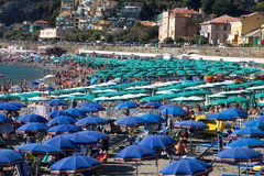 在Levanto,意大利海滩的绿色和蓝色沙滩伞  免版税库存照片