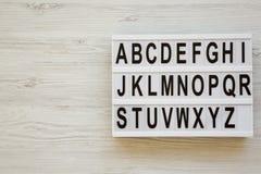 在lightbox的英语字母表在白色木表面,顶视图 信件从A到Z 回到概念学校 从上,平 免版税库存照片