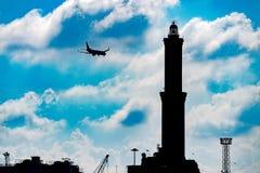 在Lightouse Lanterna热那亚镇意大利标志附近的飞机 免版税库存图片