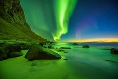 在Lofoten海岛靠岸在有强的绿色北极光的挪威 免版税库存照片