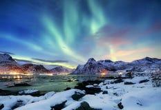 在Lofoten海岛,挪威上的极光borealis 在山上的绿色北极光 与极光的夜空 夜冬天l 免版税库存照片
