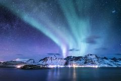 在Lofoten海岛,挪威上的极光borealis 在山上的绿色北极光 与极光的夜空 夜冬天l 库存照片