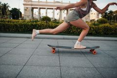 在longboard的年轻运动的妇女骑马在公园 库存图片