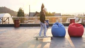 在longboard的美女乘驾 夹克衬衣和蓝色牛仔裤乘驾的行家女孩在a屋顶的一longboard  股票录像