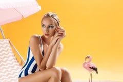 在looing夏天的装饰的俏丽的时装模特儿佩带的泳装  图库摄影