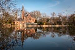 在Love湖, Minnewater公园的中世纪城堡在布鲁日,比利时 免版税库存照片