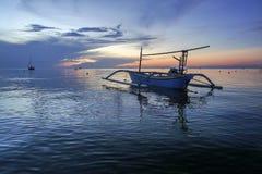在Lovina海滩,在日出期间的巴厘岛的美丽的小船与海豚 免版税库存图片