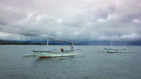 在Lovina的舷外架小船在有风雨如磐的云彩的巴厘岛 图库摄影
