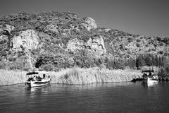 在Lycian坟茔背景的两条旅游小船古老 库存照片