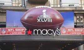 在Macy在百老汇的s先驱广场的巨型橄榄球在超级杯XLVIII星期期间在曼哈顿 图库摄影