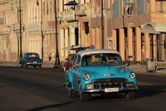 在Malecon日落的蓝色老美国汽车 库存图片