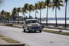 在Malecon,古巴的老美国汽车驱动 免版税库存图片