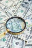 在manifying的玻璃下的金钱 免版税库存图片