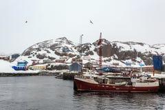 在Maniitsoq村庄码头的渔船有五颜六色hous的 免版税库存照片