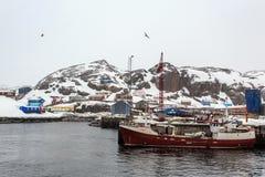 在Maniitsoq村庄码头的渔船有五颜六色hous的 库存图片