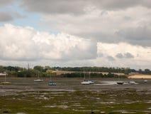 在manningtree的出海口场面与被停泊的小船浪潮覆盖土地 免版税库存图片