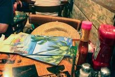 在Margaritaville的一张桌有菜单的和帽子和调味品基韦斯特岛佛罗里达美国 免版税库存照片