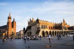 在Mariacki大教堂的落日和在集市广场的布料霍尔在克拉科夫波兰 免版税图库摄影