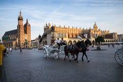 在Mariacki大教堂的落日和在集市广场的布料霍尔在克拉科夫波兰 免版税库存照片