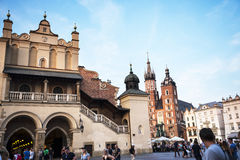 在Mariacki大教堂的落日和在集市广场的布料霍尔在克拉科夫波兰 库存图片