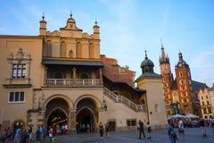 在Mariacki大教堂的落日和在集市广场的布料霍尔在克拉科夫波兰 图库摄影