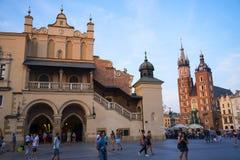 在Mariacki大教堂的落日和在集市广场的布料霍尔在克拉科夫波兰 免版税库存图片