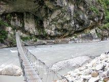 在Marsyangdi河的桥梁在Tal村庄-尼泊尔附近 免版税库存图片