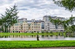 在Martynov堤防的大厦和Srednyaya的Nevka孤独的渔夫开户 库存照片