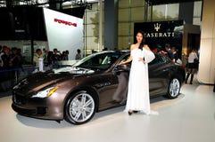在Maserati Quattroporte跑车的时装模特儿 免版税库存照片