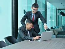 在mee的膝上型计算机前面的亚裔商人 图库摄影