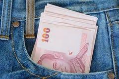在men s蓝色牛仔裤口袋的100张泰国钞票 库存照片
