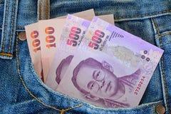 在men s蓝色牛仔裤的500张和100张钞票装在口袋里 库存图片