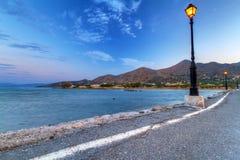 在Mirabello海湾附近的空的路在黄昏 免版税库存图片
