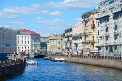 在Moika河的游览小船在绿色桥梁,圣彼德堡,俄罗斯附近 免版税库存照片